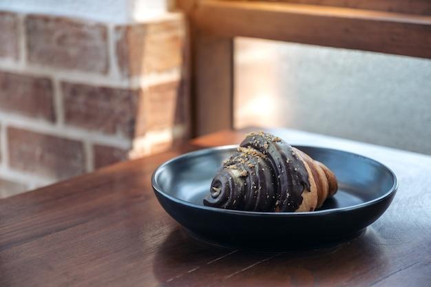 Um pedaço de croissant de chocolate em uma placa preta na mesa de madeira de uma padaria