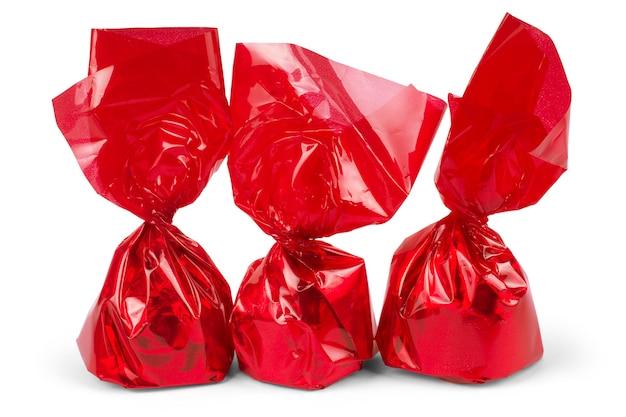 Um pedaço de doce ou uma pastilha para tosse embrulhado em um invólucro de celofane vermelho brilhante sobre um fundo branco