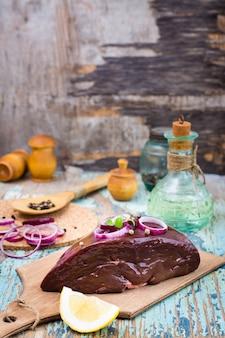 Um pedaço de fígado de carne crua em uma tigela com ingredientes para cozinhar em uma mesa de madeira