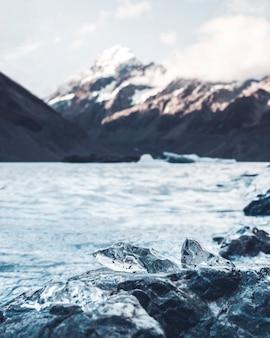 Um pedaço de gelo do que anteriormente era a geleira de mount cook derrete na orla do lago devido ao impacto do aquecimento global e das mudanças climáticas.