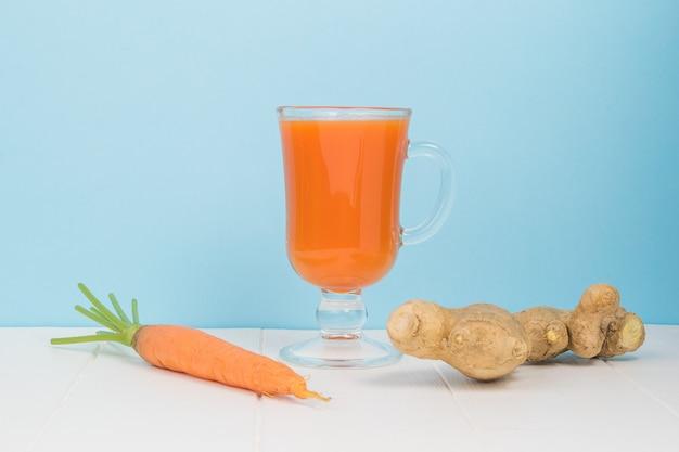 Um pedaço de gengibre, cenoura e um copo de smoothies em uma mesa branca sobre um fundo azul.