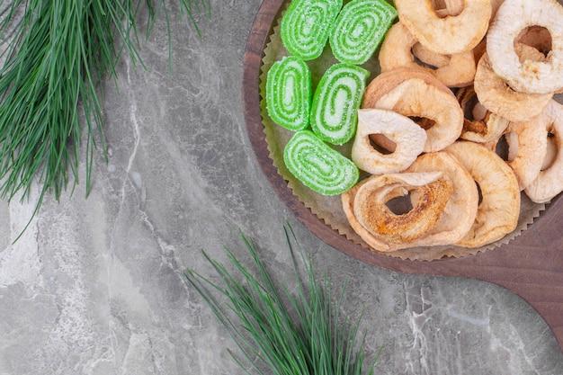 Um pedaço de madeira com geleias verdes doces e frutas secas de maçã.