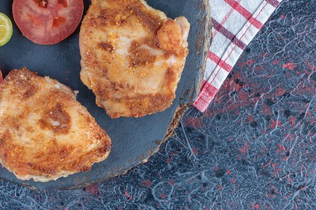 Um pedaço de madeira de costeletas de frango com uma fatia de tomate.