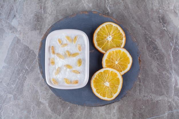Um pedaço de madeira de mingau de aveia saudável com passas e fatias de frutas de laranja.