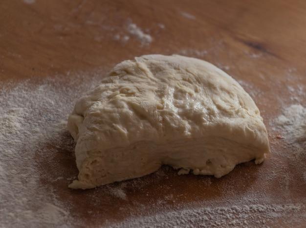 Um pedaço de massa de fermento em uma placa de madeira de cozinha rural