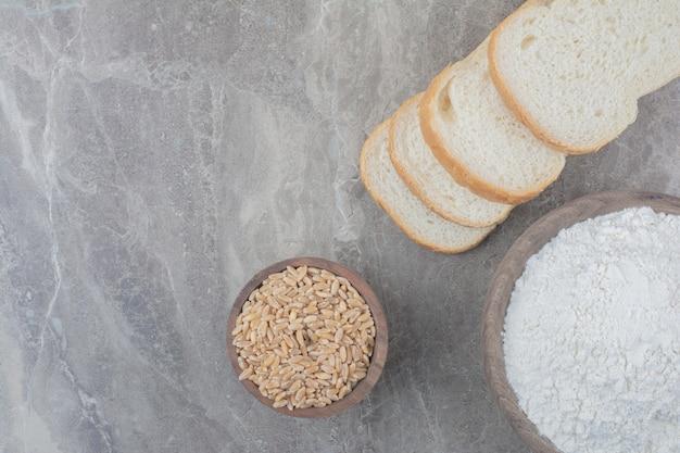 Um pedaço de pão branco com grãos de aveia e farinha no fundo de mármore.