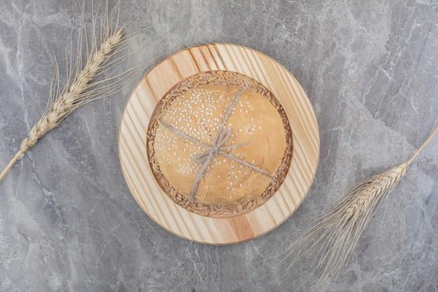 Um pedaço de pão branco com grãos de aveia na placa de madeira