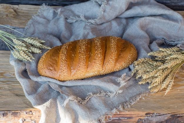 Um pedaço de pão branco e espigas em uma mesa de madeira