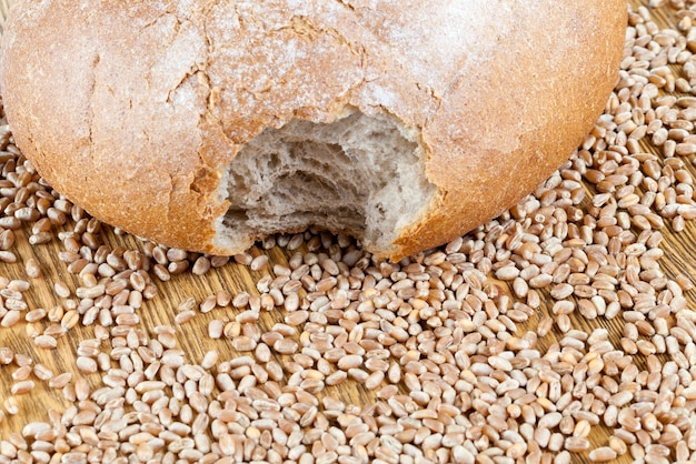 Um pedaço de pão de trigo mordido sobre uma mesa de madeira com grãos inteiros