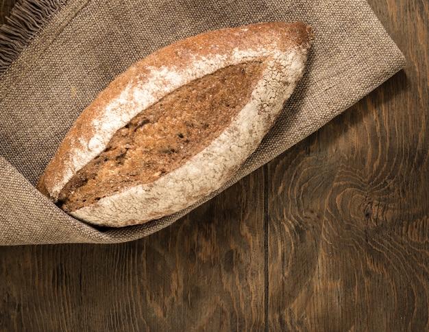 Um pedaço de pão em um guardanapo de pano e tábuas de madeira, vista de cima