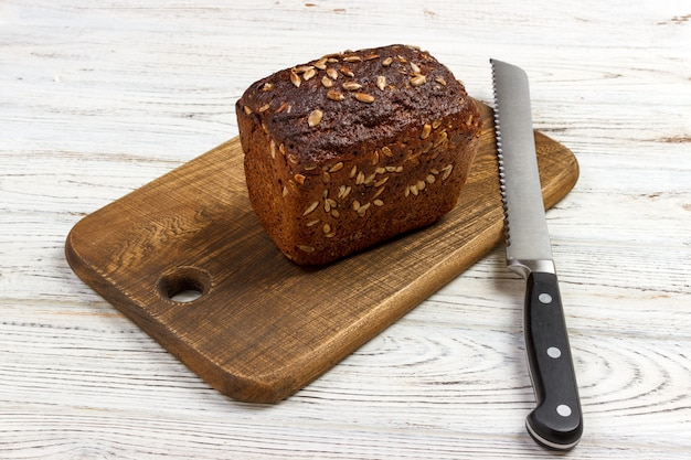 Um pedaço de pão em uma placa de corte com faca
