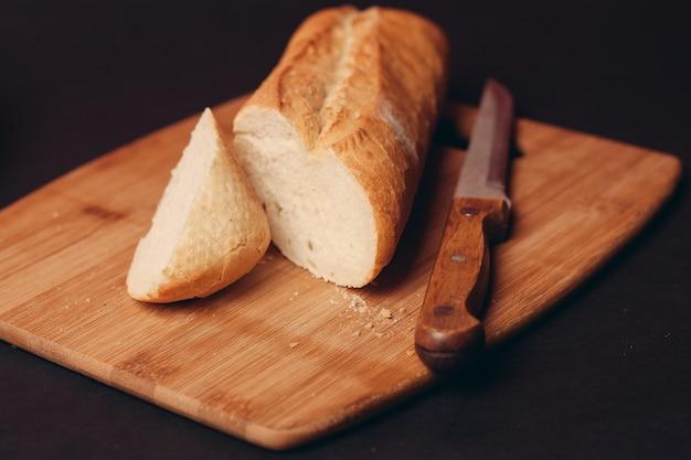 Um pedaço de pão fatiado em uma placa e fundo escuro de produtos de confeitaria de bolos. foto de alta qualidade