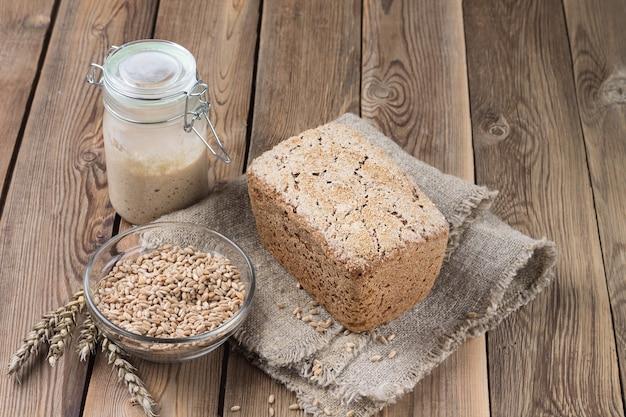 Um pedaço de pão feito de farinha de espelta em um fermento de farinha em uma mesa de madeira natural.