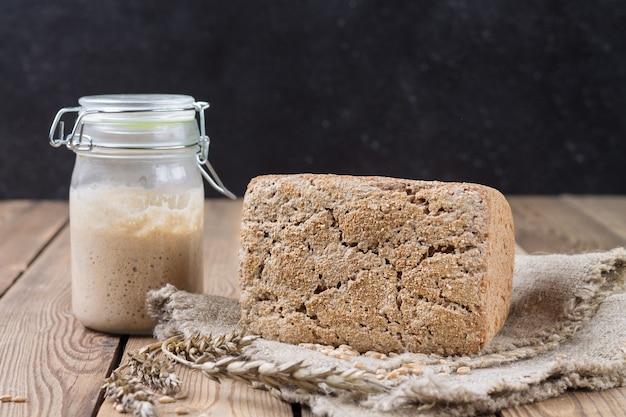 Um pedaço de pão fermentado feito de farinha de espelta em uma entrada de farinha em uma mesa de madeira natural.