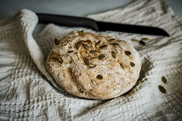 Um pedaço de pão integral caseiro em uma toalha bege e uma faca preta