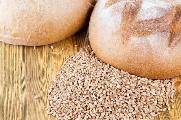 Um pedaço de pão integral e grãos de trigo empilhados sobre uma mesa de madeira, close-up de cima