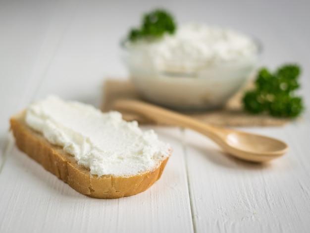 Um pedaço de pão integral emplastrado creme de queijo cottage em uma mesa branca vintage.