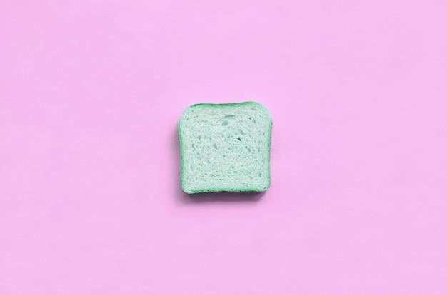 Um pedaço de pão verde encontra-se na textura de papel de cor rosa pastel moda