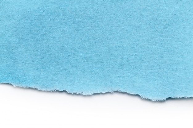 Um pedaço de papel azul rasgado. observe as tiras de papel para texto ou mensagem presas em um fundo azul