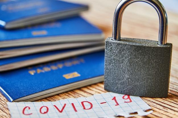 Um pedaço de papel com a inscrição covid-19, cadeado e passaporte na superfície de madeira. coronavírus e conceito de viagens. fechando fronteiras entre países devido a vírus. fechar-se