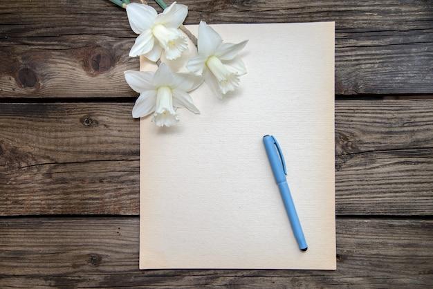 Um pedaço de papel com caneta e narcisos brancos sobre fundo de madeira