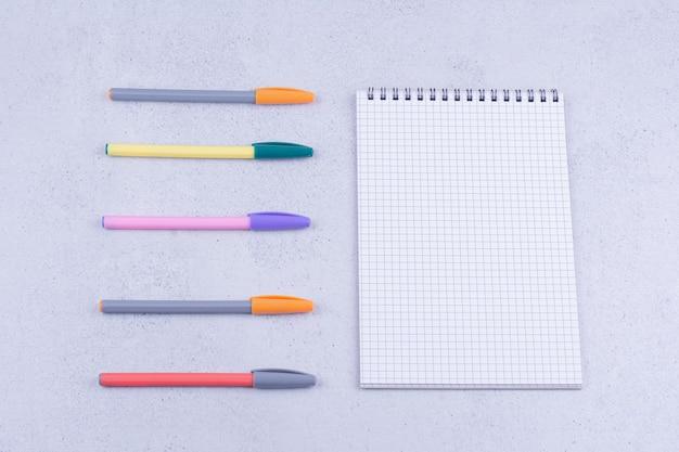 Um pedaço de papel com lápis multicoloridos ao redor