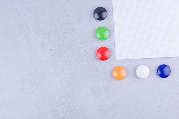 Um pedaço de papel em branco com alfinetes coloridos ao redor.