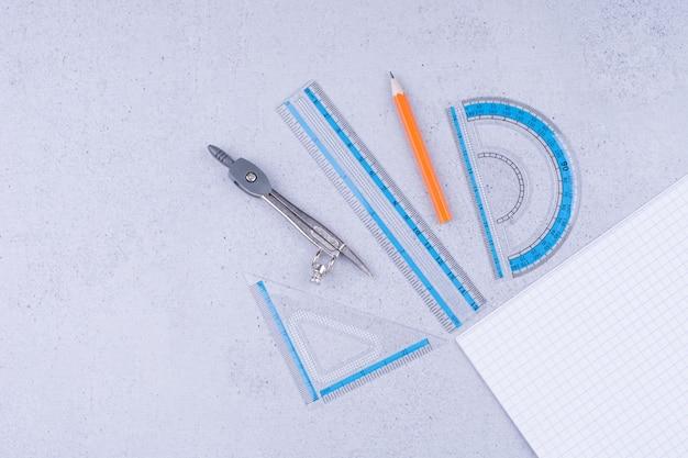 Um pedaço de papel em branco com ferramentas de desenho ao redor.