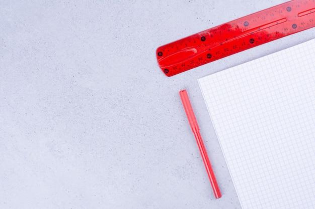 Um pedaço de papel em branco com régua vermelha e lápis de carvão.