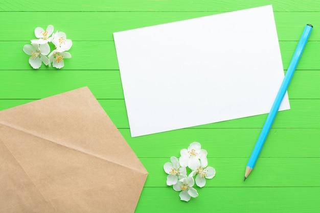 Um pedaço de papel em branco com um envelope sobre fundo verde de madeira