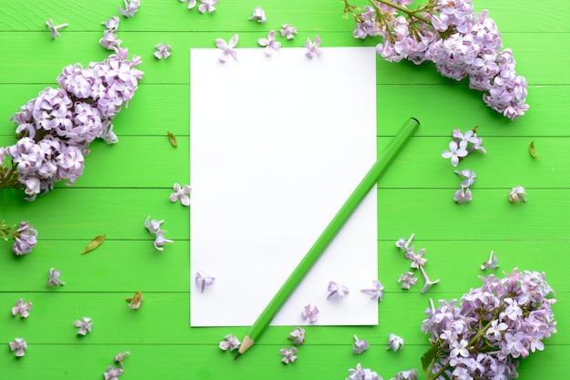 Um pedaço de papel em branco sobre um fundo verde de madeira