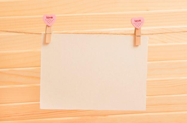 Um pedaço de papel em prendedores de roupa com corações