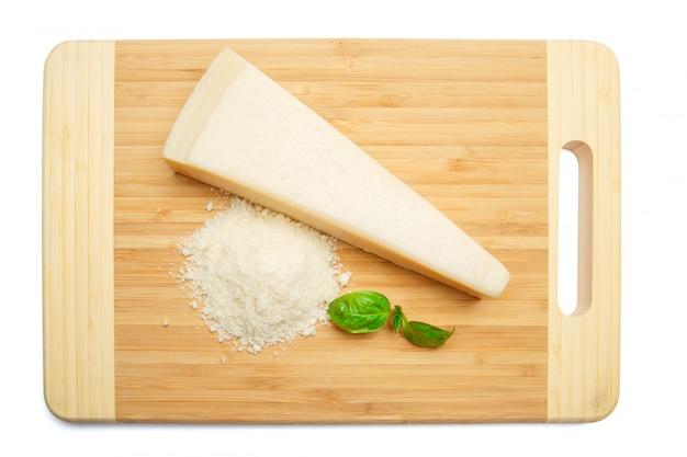 Um pedaço de parmesão e queijo ralado na mesa de corte mesa branca