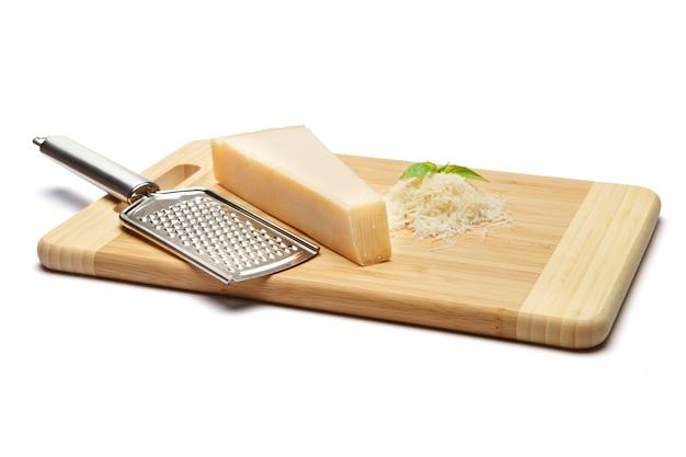 Um pedaço de parmesão e queijo ralado na tábua