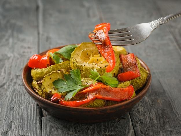 Um pedaço de pimenta assada em um garfo e uma tigela de legumes cozidos. prato vegetariano. alimentos vegetais naturais. a vista do topo. postura plana.
