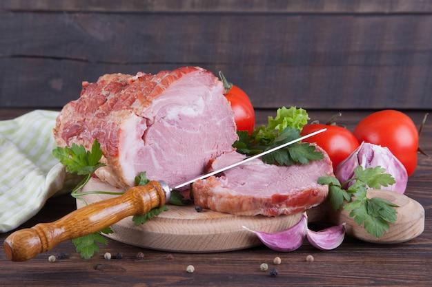 Um pedaço de presunto e legumes em um fundo de madeira. produto meatworks