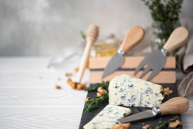 Um pedaço de queijo azul dor com tomilho e nozes em uma tábua de queijos com facas