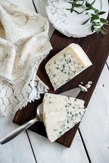 Um pedaço de queijo azul dor em uma tábua de queijos com facas queijos azuis delicadeza.