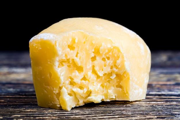 Um pedaço de queijo duro com buracos, um close-up de um queijo quebrado em pedaços com sua própria estrutura