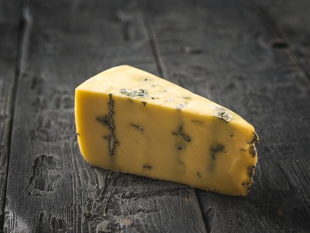 Um pedaço de queijo fresco com mofo azul sobre uma mesa de madeira. delicadeza de queijo. um molde útil