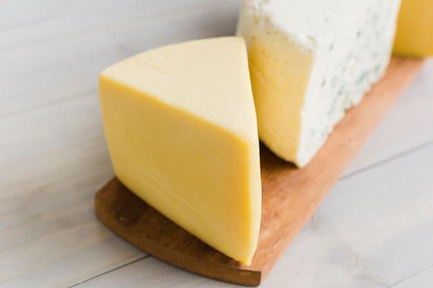 Um pedaço de queijo na tábua sobre a mesa de madeira