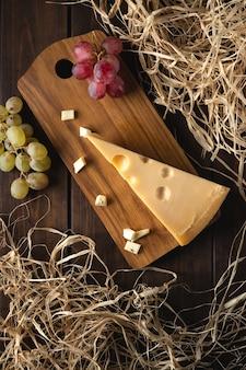 Um pedaço de queijo suíço amarelo com buracos e um galho de uvas vermelhas em uma placa de corte contra uma superfície preta