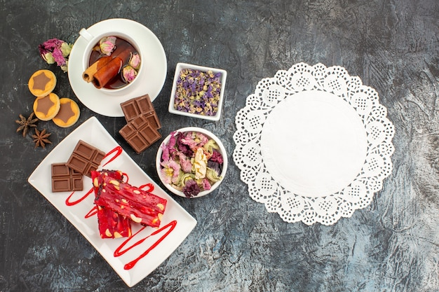 Um pedaço de renda com um prato de chocolates e chá de ervas e flores secas com biscoitos em fundo cinza
