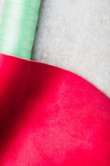 Um pedaço de tecido de costura com carretel de linha