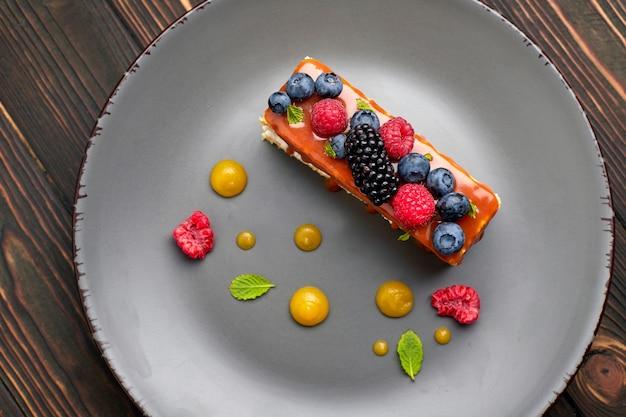 Um pedaço de torta, bolo de mel com frutas frescas, hortelã e caramelo, em uma mesa de madeira