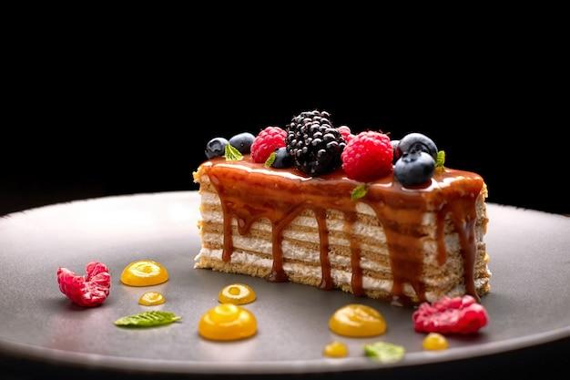 Um pedaço de torta, bolo de mel com frutas frescas, hortelã e caramelo