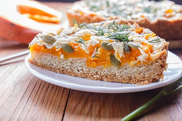 Um pedaço de torta de abóbora doce com queijo e endro no fundo de madeira marrom