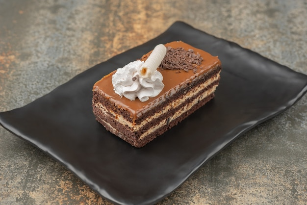 Um pedaço de torta doce no prato escuro