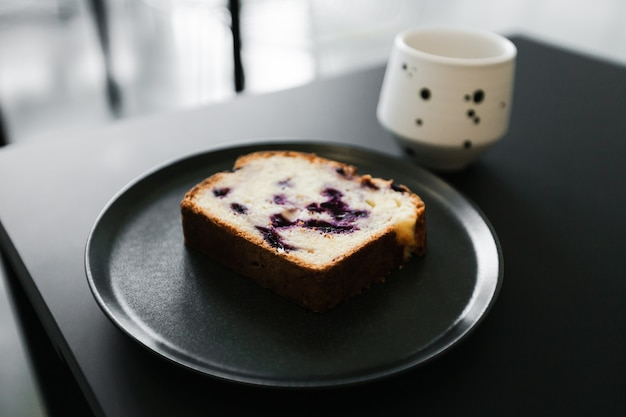 Um pedaço de um bolo de frutas com frutas e uma xícara de café em uma mesa preta