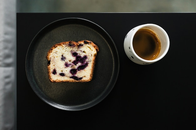 Um pedaço de um bolo de frutas com frutas e uma xícara de café expresso em uma mesa preta